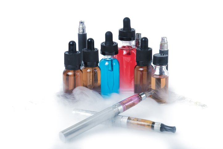 Two electronic cigarettes with glass e-liquid bottles with smoke on white background